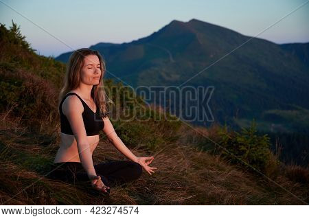 Side View Of Woman Practicing Yoga In Lotus Pose In The Mountains. Meditating Female Is Taking A Dee