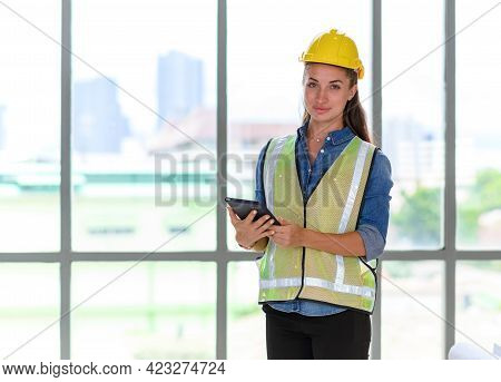 Portrait Of Female Construction Engineer Workers In Yellow Hardhat With A Tablet Computer In Constru