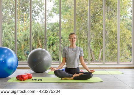 Time For Practicing Yoga. Young Attractive Woman Sitting In Ardha Padmasana Exercise, Lotus Pose On