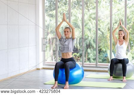 Caucasian Women Sitting And Balancing On Exercise Ball. Fitness, Sport, Training And People Concept