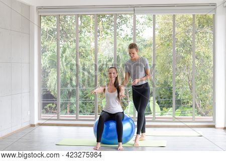 Caucasian Woman Sitting And Balancing On Exercise Ball With Trainer. Fitness, Sport, Training And Pe