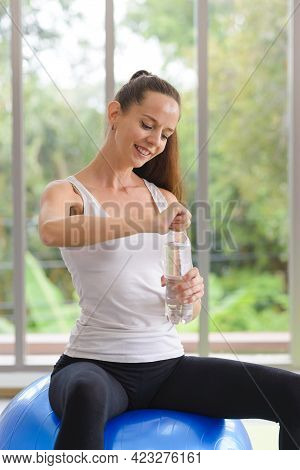 Fitness Woman Drinking Water From Bottle. Taking A Break During Training At Gym
