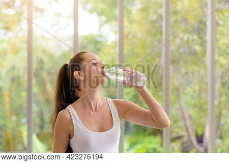 Fitness Woman Drinking Water From Bottle. Taking A Break During Training At Gym With Copy Space