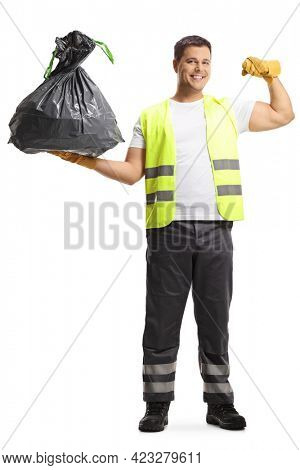 Full length portrait of a waste collector in a uniform and gloves holding a bin bag and showing muscles isolated on white background