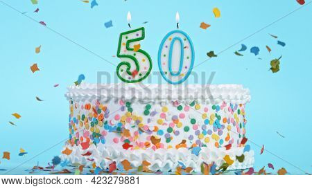 Colorful tasty birthday cake with candles shaped like the number 50.