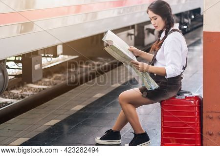 Asian Woman Pregnant Tourist Waiting Sit On The Bench Look At The Map With Red Suitcase At Railway S