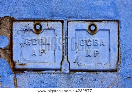 Two Metal Box And A Blue Broken Wall