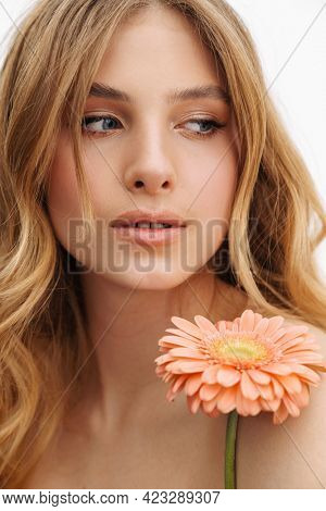 Half-naked ginger woman posing with gerbera flower isolated over white background