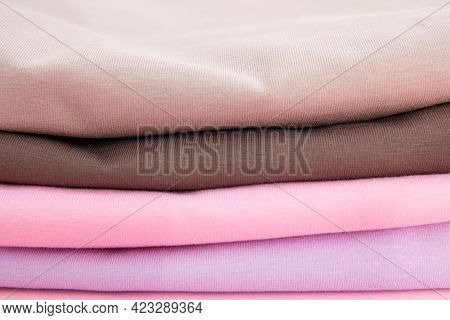 Background Of Colorful Cotton Folded Clothes Stack. Stack Of Multicolored Clothes. Set Of Clothes In