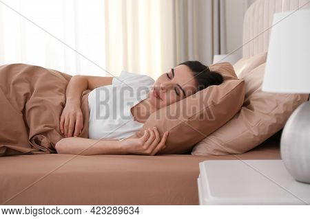 Young Woman Sleeping In Bed With Brown Linens At Home