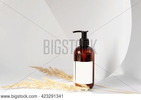 Bottle With Dispenser For Cosmetic Products With Blank Label On White Background With Unfolded Sheet