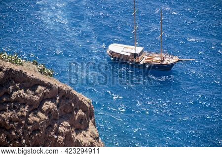 Traditional Gulet Boat In Santorini Island, Aerial View From The Top Of The Caldera