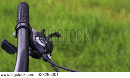 Mountain Bike Steering Wheel On Green Grass Background. Details Of Sporting Events. Close Up Black M