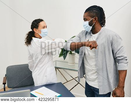 African American Man And His Doctor Wearing Medical Masks Greeting Each Other By Elbow Bumping At Do