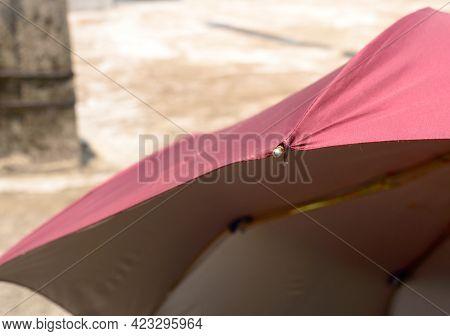 Extreme Close Up Of Uv Umbrella In The Summer Sun. Red Color Beach Umbrella Blocking The Sunlight. S