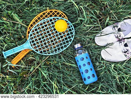 Summer Flat Lay On Green Grass With Rackets And Ball, Glass Bottle Of Water And Summer White Shoes,