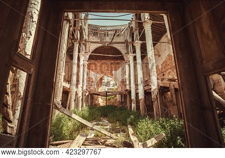 Ruins Of Old Abandoned Church With Brick Walls. Large Ruined Building With Arch And Ceiling.