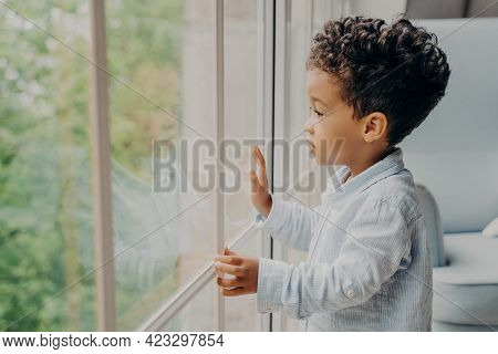 Side View Of Focused Adorable Sweet Kid Boy Looking Outside Through Window With Surprised And Intrig