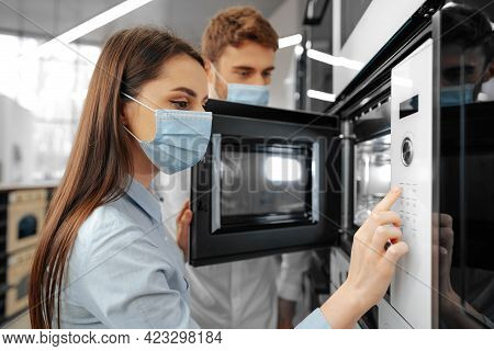 Young Couple Wearing Medical Masks In Hypermarket With Home Appliances