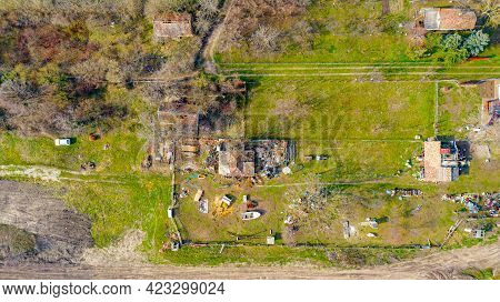 Above Top View On Fenced Messy Yard, Old House With Scattered Things Around, Dirty Rural Road Goes A