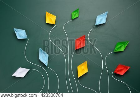Group Of Multi-colored Paper Boats Flies In Different Directions On A Green Background, Top View. In