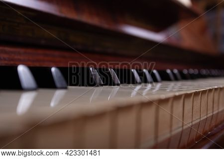 Close Up Of Black And White Piano Keys. Selective Focus. Vintage Brown Piano.