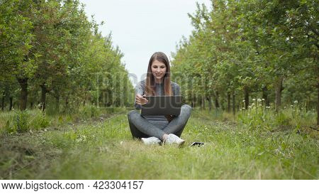 Girl Sitting In Park Or Forest, Opening Laptop On Nature. It Specialist Working At Self Isolation Ou