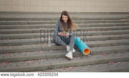 Fitness Woman Using Phone With Workout App Exercising Sitting At City On The Stairs. Sport And Techn