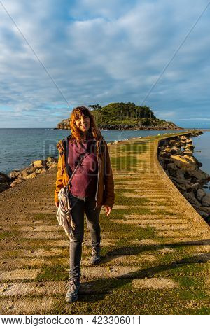 A Young Woman On The Catwalk To Go To San Nicolas Island At Low Tide From Isuntza Beach In Lekeitio,