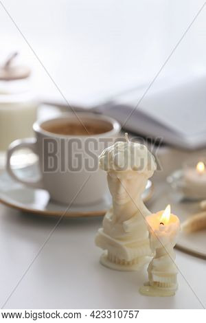 Beautiful David Bust Candles And Cup Of Hot Drink On  White Table Indoors, Space For Text