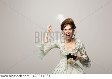 Kyiv, Ukraine - April 22, 2021: Excited Woman In Vintage Dress Showing Win Gesture While Holding Gam