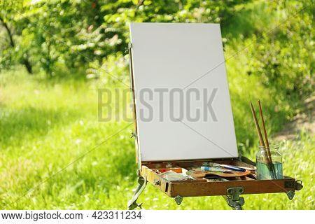 Easel With Blank Canvas And Painting Equipment In Countryside