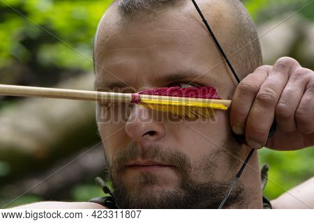 Portrait Of A Man Aiming An Arrow From A Bow In The Forest, Close-up, Selective Focus. Concept: Men'