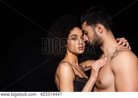 Sexy African American Woman Looking At Camera While Embracing Shirtless Man Isolated On Black