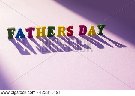 Child's Toy Letters Spelling Fathers Day With A Large Shadow On Purple Background.