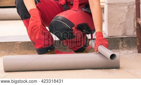 Woman In Dungarees Carrying Plastic Pipes On Her House Construction Site, Building New Home.