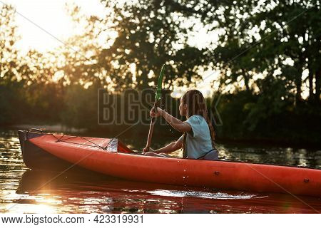 Young Woman Enjoying A Day Kayaking In A Lake Surrounded By Nature On A Late Summer Afternoon. Kayak