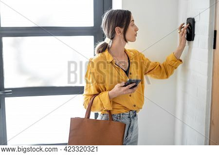 Woman Enters A Code On The Alarm Keyboard At The Hallway Indoors. Concept Of Home Security And Smart