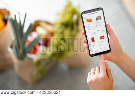 Holding Phone With Running E-shop Application And Bags Full Of Fresh Food On The Background. Shoppin