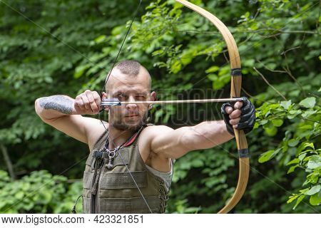 Portrait Of A Stern Man Shooting An Arrow From A Bow In The Forest. Concept: Men's Hobbies, Survival