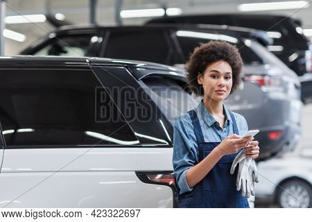 Positive Young African American Mechanic In Overalls Standing With Smartphone In Auto Repair Service