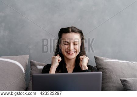 Portrait Of Young Woman Sitting With Laptop Computer On Comfort Couch In Living Room, Raised Fists U