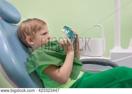 Boy Man Child At Dentist In Chair Look At White Teeth. Curious, Serious Look. Oral Health And Hygien