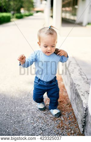 Little Girl With A Ponytail Walks Along The Road In The Park And Carries A Pebble On Her Shoulder