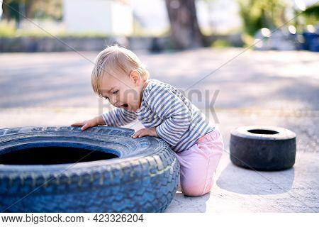 Child Is Kneeling And Leaning On A Car Tire In A Parking Lot