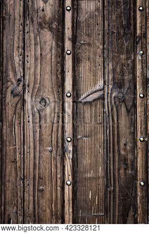 Ancient Wooden Door With Metal Rivets In Contrast