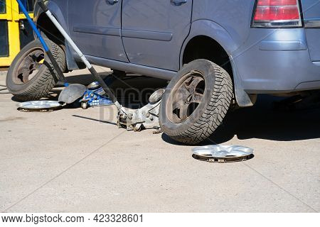 Car Mechanic Screwing Or Unscrewing Car Wheel Of Lifted Automobile By Pneumatic Wrench At Repair Ser
