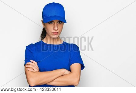 Young hispanic girl wearing delivery courier uniform skeptic and nervous, disapproving expression on face with crossed arms. negative person.