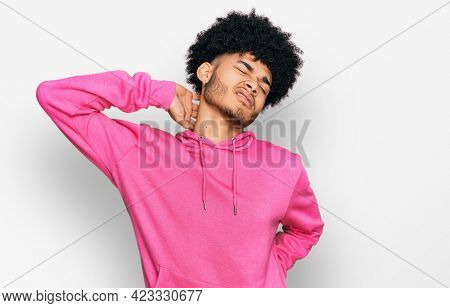 Young african american man with afro hair wearing casual pink sweatshirt suffering of neck ache injury, touching neck with hand, muscular pain