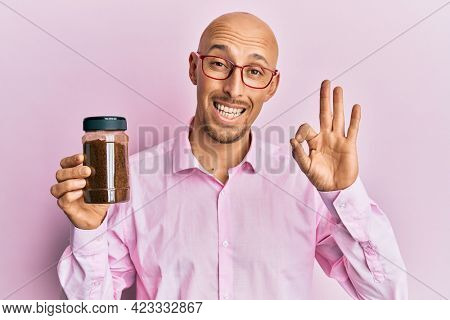 Bald man with beard holding soluble coffee doing ok sign with fingers, smiling friendly gesturing excellent symbol
